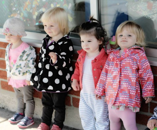 toddler girls lined up against wall outdoors
