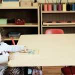 girl sitting at daycare table with puzzle